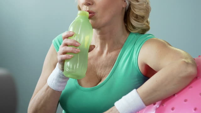 Aged female resting elbow on fitness ball and drinking water after exercising video