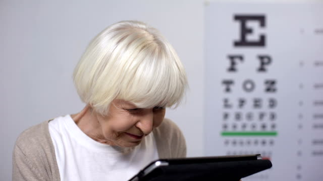 Aged lady putting on glasses, smiling and reading from tablet, focusing vision Aged lady putting on glasses, smiling and reading from tablet, focusing vision eye chart stock videos & royalty-free footage