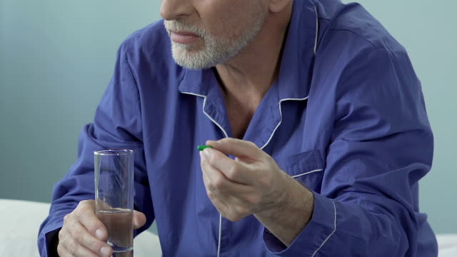 Aged male holding pill in one hand, glass of water in another, sighing heavily video