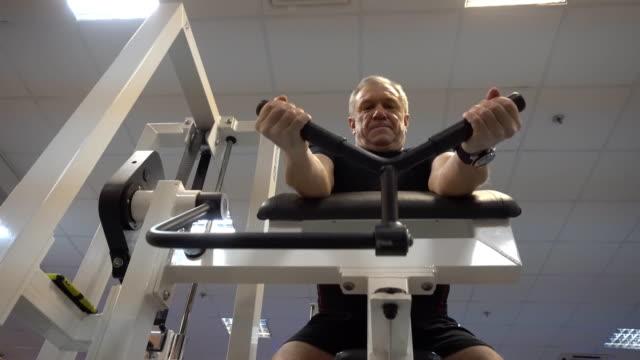 stockvideo's en b-roll-footage met leeftijd man in opleiding op de nieuwste technogym fitnessapparatuur - fitnessapparaat