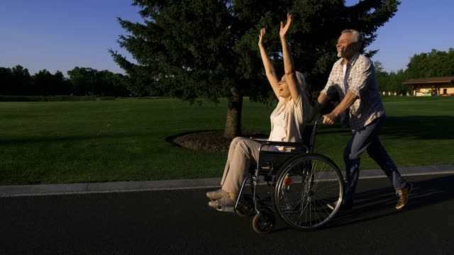 Aged man running while pushing wife in wheelchair Side view of funny and cheerful happy senior couple enjoying outdoors. Senior bearded husband running and pushing wife in wheelchair. Happy woman raising arms and having fun. Steadicam shot pushing wheelchair stock videos & royalty-free footage