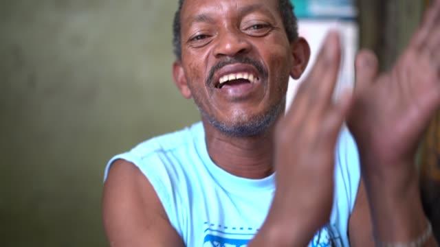 vídeos de stock e filmes b-roll de aged man singing and playing samba with hands - bateria instrumento de percussão