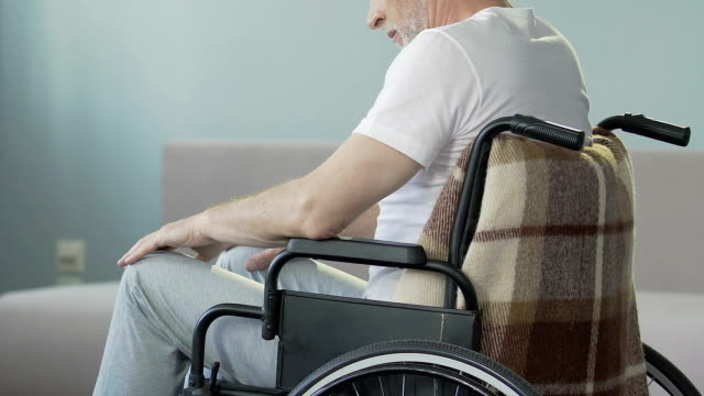 Aged man sitting in wheelchair looking at legs and nodding, lost ability to walk video