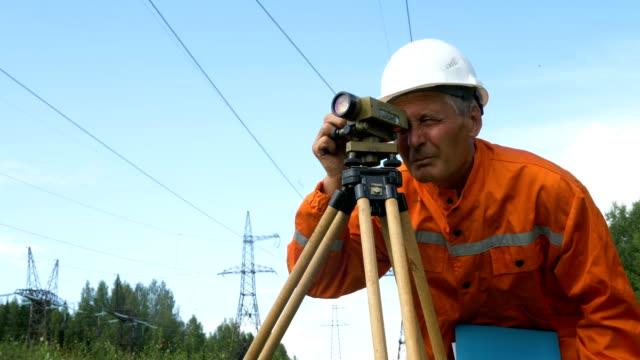 aged surveyor looks through dumpy level under power lines - vídeo