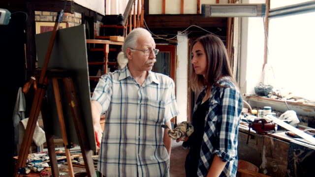 Aged teacher painter, painting with young girl video
