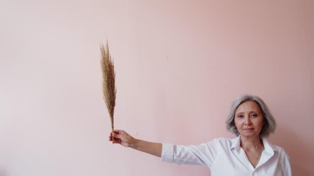 åldrad kvinna som håller torrt gräs - mature women studio grey hair bildbanksvideor och videomaterial från bakom kulisserna
