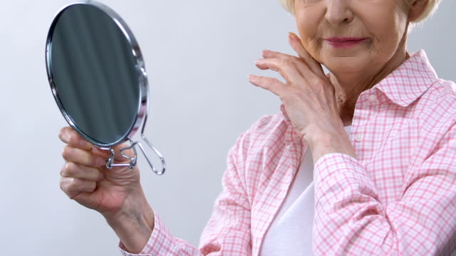 Aged woman looking in mirror, touching wrinkled face, thinking about lost beauty