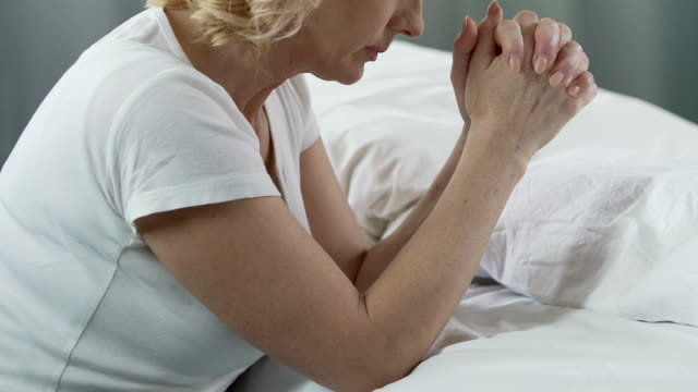 Aged woman praying at her bed, religious values and convictions, faith in God video