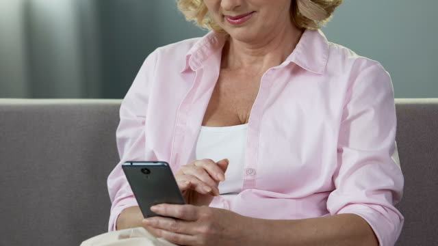 Aged woman scrolling mobile phone screen, smiling at received photos, gadget video