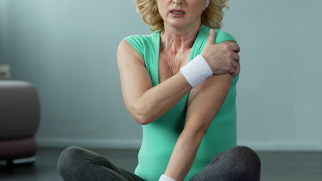 Aged woman sitting cross-legged and stretching arms, muscle cramp, exercising video