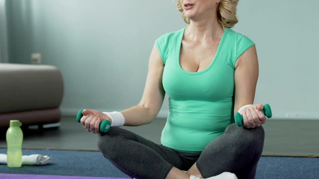 Aged woman sitting on floor cross-legged, flexing arms holding dumbbells, sport video