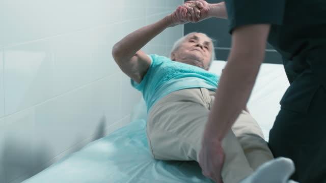 vidéos et rushes de femme âgée s'asseyant sur le lit de thérapie avec l'aide de docteur - infirmier