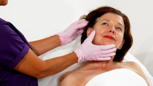 Aged woman smiling while cosmetologist examining her face Cropped shot of a middle aged female patient smiling joyfully, while professional cosmetologist examining her skin before facial treatment. Skincare, rejuvenation, anti-aging concept. dermatology stock videos & royalty-free footage