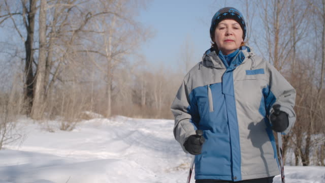 Aged woman walking in the forest by nordic walk at winter landscape, slow motion video