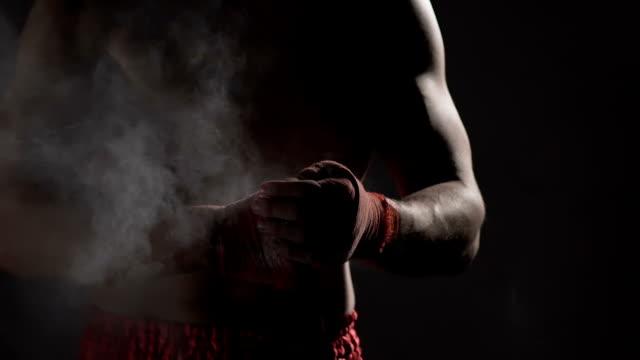 vídeos de stock e filmes b-roll de aggressive boxer preparing for fight, clapping together hands with talcum powder - boxe tailandês