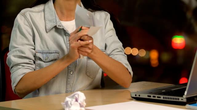 vídeos de stock e filmes b-roll de aggressive demotivated female crumpling paper, failing to develop new idea - amarrotado
