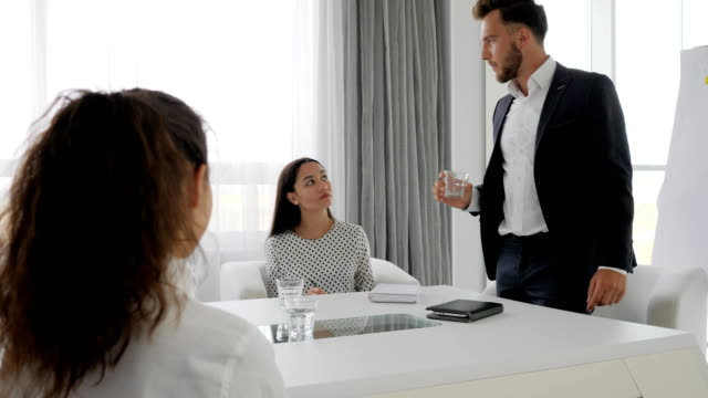 aggressive director and female employees at table in office, evil boss hold in hand glass water in conference room video