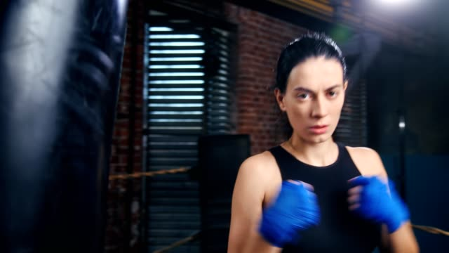 Aggressive female kickboxer with drops of sweat on face in blue wrapped hands posing at dark gym