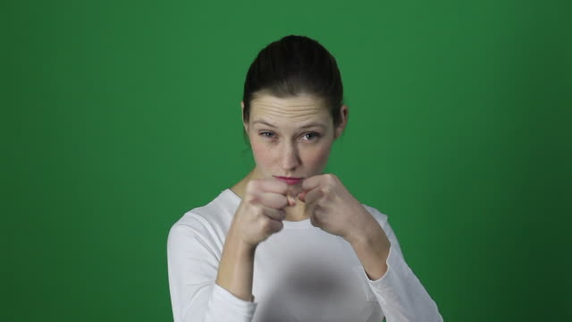 Aggressive furious woman boxing at camera. Aggressive furious woman boxing at camera. Studio shot, isolated in light green background sleeve stock videos & royalty-free footage