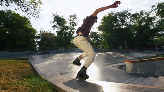 Aggressive Inline roller skater doing tricks in concrete skatepark outdoors, slow motion