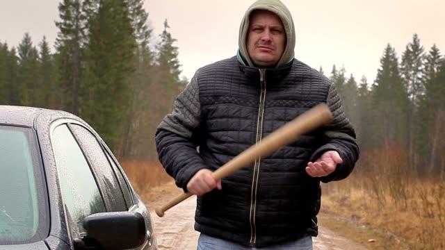 Aggressive man with a baseball bat near car in rainy day video