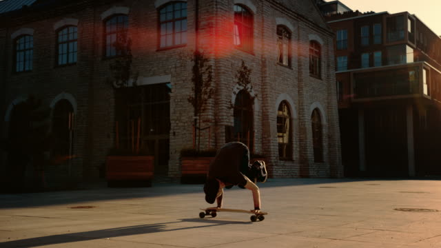 agile professional skater stands on the hands on his skateboard. strong guy doing handstand tricks on a longboard. in the background fashionable hipster city district street - postawa filmów i materiałów b-roll