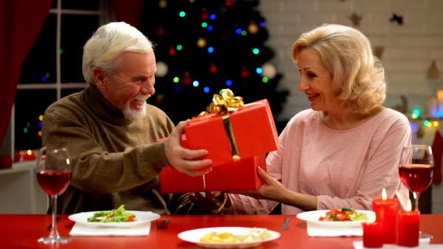åldrande par utbyta presenterar på julafton anbud relationer genom åren - wine box bildbanksvideor och videomaterial från bakom kulisserna
