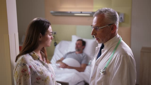 Aging doctor telling bad news to patient's wife Side view of worried woman listening to elderly physician standing in hospital ward while sick husband sleeping on background. Unhappy wife hearing negative examination results from doctor husband stock videos & royalty-free footage
