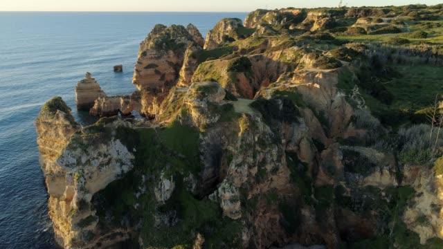 aglarve, portekiz. gün batımı sırasında atlantik okyanusu kayalık ve yosunlu sahil üzerinde uçan. hava çekimi, 4k - minas gerais eyaleti stok videoları ve detay görüntü çekimi