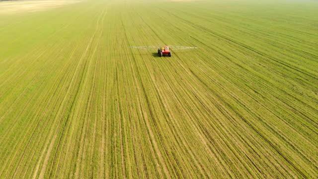vídeos y material grabado en eventos de stock de maquinaria agrícola rocía fertilizante mineral sobre un campo verde, natural, fondo primaveral - mineral