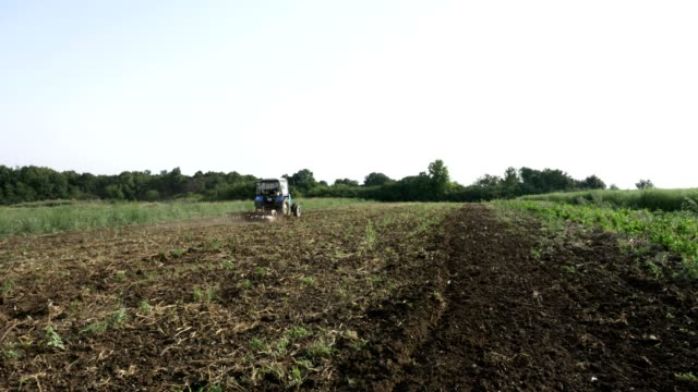 Agricultural tractor sowing and cultivating field at organic eco farm video