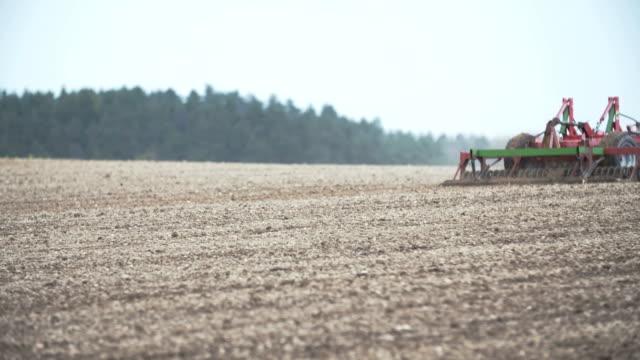 vidéos et rushes de à l'aide de tracteurs agricoles herses tout en labourant le champ. - seigle grain