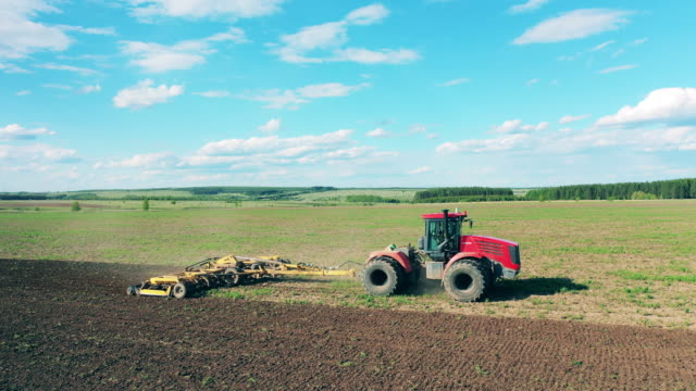 Agricultural tractor works on a field, plowing. Agricultural tractor works on a field, plowing. 4K harrow agricultural equipment stock videos & royalty-free footage