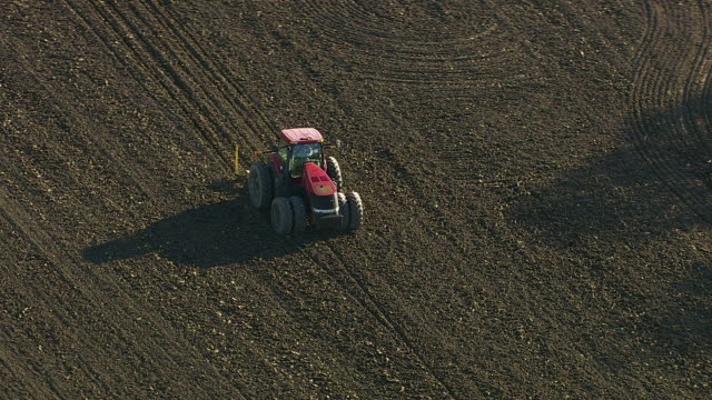 Agriculture, aerial shot of tractor plowing field