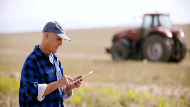 vidéos et rushes de agriculture, agriculteur à l'aide de tablette numérique sur le champ pendant la récolte - équipement agricole