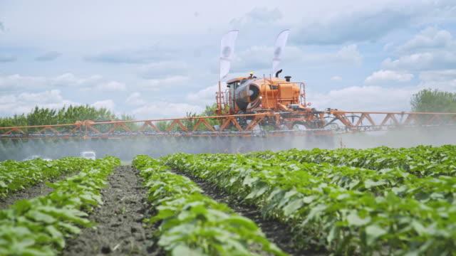 vídeos de stock, filmes e b-roll de pesticidas de fertilizante agricultura pulverização. fertilizar as plantas. agricultura de fazenda - culturas