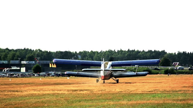 agriculturial airplane landing in a field near the forest, the forest airfield video