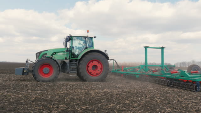 Agrobusiness - tractor running in the field in the spring 3-axis stabilized video video