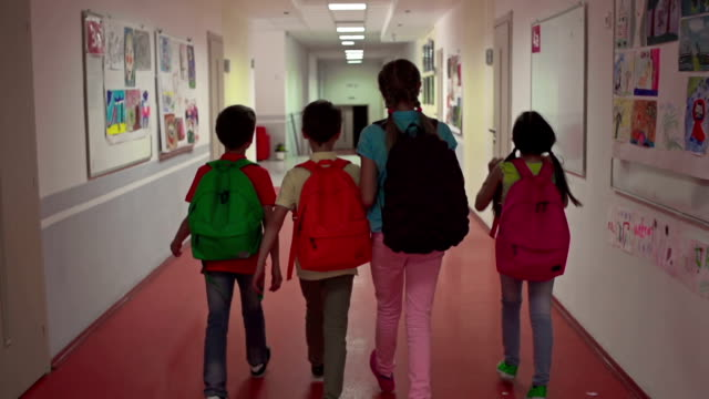 Ahead to Knowledge Camera following four kids with schoolbags going along the school corridor and joyously chatting in slow motion elementary age stock videos & royalty-free footage