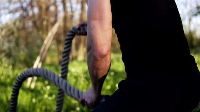 Aiming footage of a male arms waving battle ropes. Aiming footage of a male arms waving battle ropes. durability stock videos & royalty-free footage