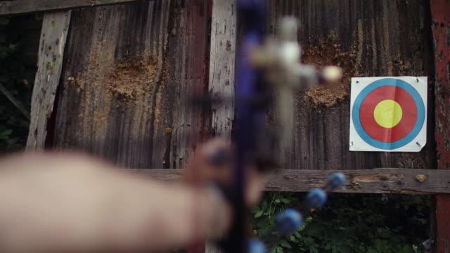 vidéos et rushes de viser d'un arc à la cible. gros plan. - tir à l'arc