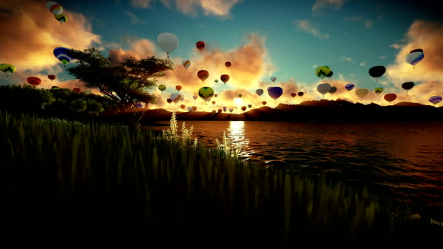 Air balloons flying over beautiful lake and green meadow surrounded by mountains, sunrise travelling shot video