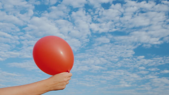luften kommer från den röda air ballongen och det blir halta. mot bakgrund av den blå himlen - platt bildbanksvideor och videomaterial från bakom kulisserna