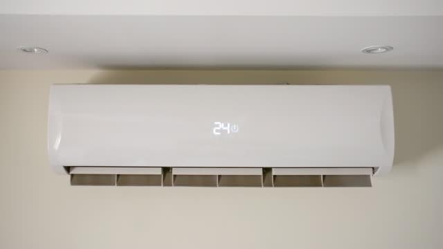 vídeos de stock, filmes e b-roll de condicionador de ar ligado, iniciar o ar condicionado na parede do quarto, mudança de temperatura, dispositivo de arrefecimento, sistema de split - ar condicionado
