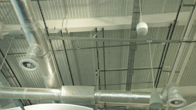 air duct ventilation pipes on ceiling of big industrial building