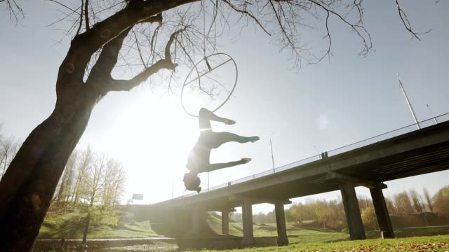 Air gymnastics woman performs acrobatics tricks on aerial hoop