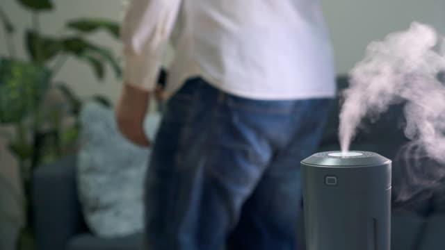 リビングルームに空気加湿器。背景にテレビを見ている男。 - 加湿器点の映像素材/bロール