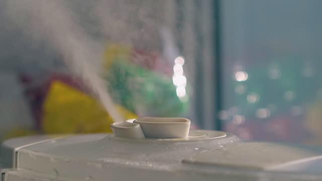 空気イオナイザーは、部屋の雰囲気を加湿するために蒸気ジェットを放出します - 加湿器点の映像素材/bロール