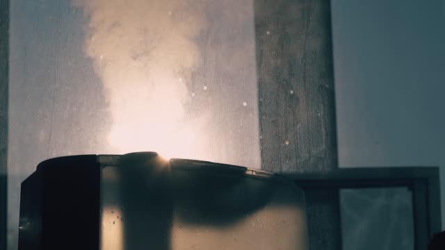 空気イオナイザーは、窓の近くのきれいな雰囲気に蒸気を放出します - 加湿器点の映像素材/bロール