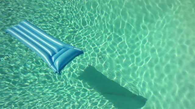 vídeos de stock e filmes b-roll de colchão de ar na piscina de água flutuante - brinquedos na piscina